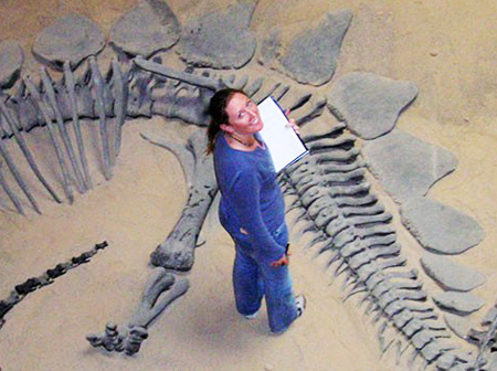 Susie studying a Stegosaurus specimen on display at the Prehistoric Museum in Price, Utah, during her PhD