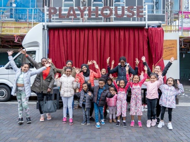 Members of Leeds Playhouse's Asmarina Choir and their children waving excitedly in front of a truck dressed as a mini moveable theatre