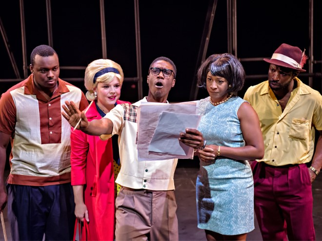 5 actors on a stage, dressed in 50s clothing. One actor reads from a piece of paper, looking ahead