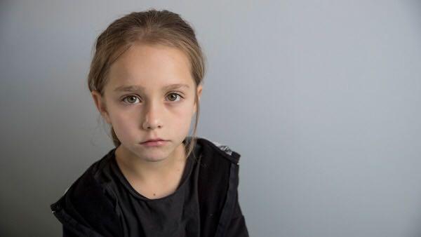 A young girl staring at the camera